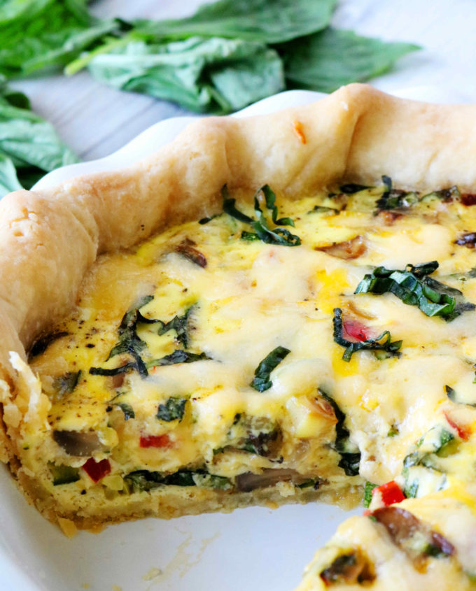 A tall, deep dish veggie quiche with a slice cut out of it.