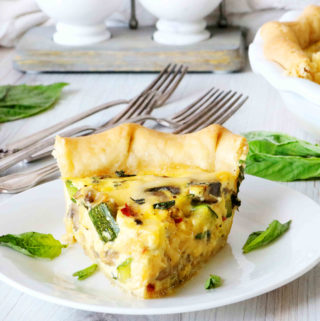 A slice of quiche sitting on a plate surrounded by basil leaves.
