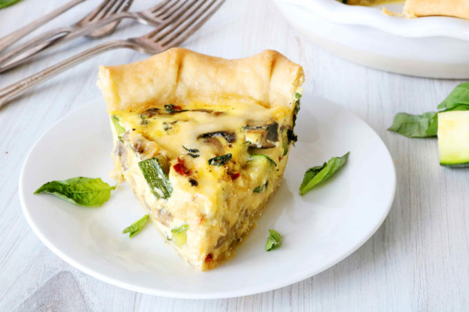 A slice of veggie quiche on a plate with forks behind it.