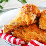 A close up shot of a fried chicken leg in a basket on top of other pieces of fried chicken.