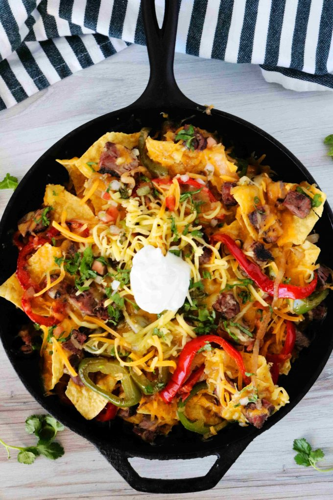 An overhead shot of fajita nachos in a skillet with chips, cheese, peppers, onions, steak, and a dollop of sour cream in the center. It has a striped towel under the handle and cilantro sprigs of cilantro around it.