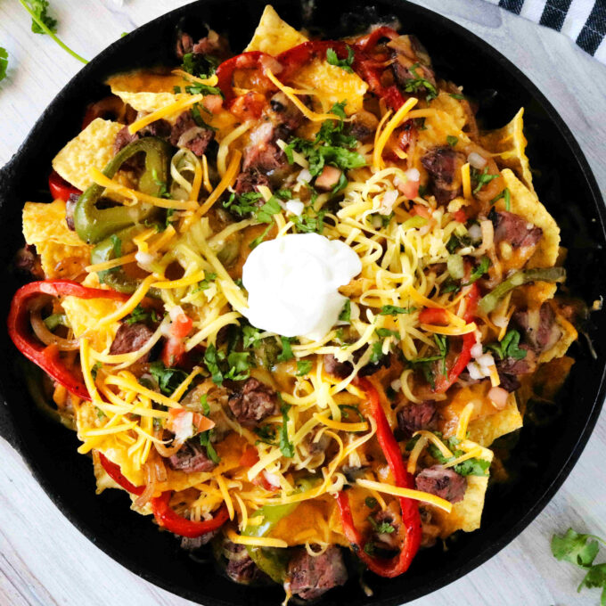 An overhead shot of fajita nachos in a skillet with chips, cheese, peppers, onions, steak, and a dollop of sour cream in the center.