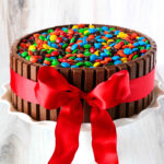 A front view of a chocolate cake, surrounded by KitKats, topped with M&Ms and tied with a red ribbon.