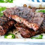 Fajita skirt steak grilled and set on a sheet pan.