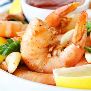 A close up shot of steamed shrimp in a bowl surrounded by lemon wedges.