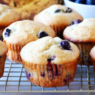 Blueberry Banana Muffins on a cooling rack with a bowl of blueberries behind them.
