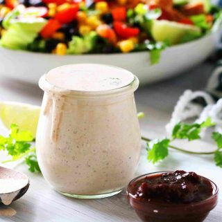 A jar of Chipotle Ranch Dressing with cilantro, chipotle peppers, and limes around it.