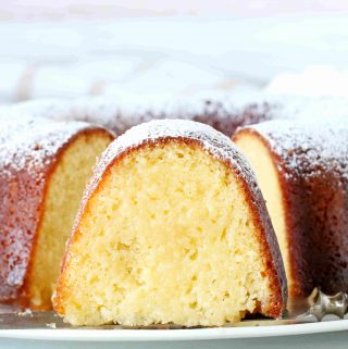A whole Kentucky Butter Cake on a platter with a slice cut out of it. There is a focal emphasis on the center slice and it is facing forward.