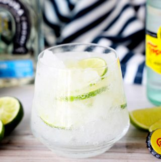 A Ranch Water Cocktail in a short glass with a bottle of tequila, lime wedges, and topo chico behind it.