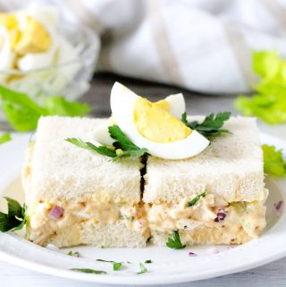 Tuna Egg Salad Sandwiches on a white plate with chopped eggs in the background.