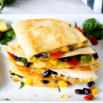 Veggie Quesadillas with corn, black beans, and peppers stacked on a white serving platter surrounded by scattered beans and corn.