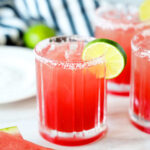 Watermelon Margaritas with a lime garnish and a salted rim and wedges of watermelon surrounded the glasses.