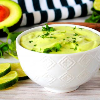 A bowl of avocado crema with a cilantro garnish and avocados, limes, and a striped napkin in the background.