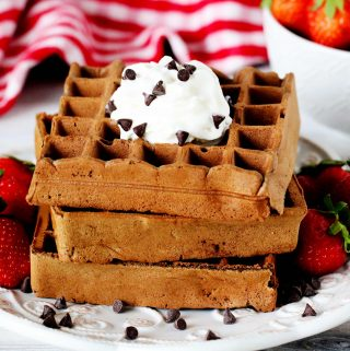 A stack of chocolate waffles on a plate surrounded by strawberries and chocolate chips with a checkered towel and a bowl of strawberries behind it.