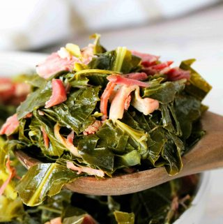Collared Greens on a spoon with shredded ham hock on top.