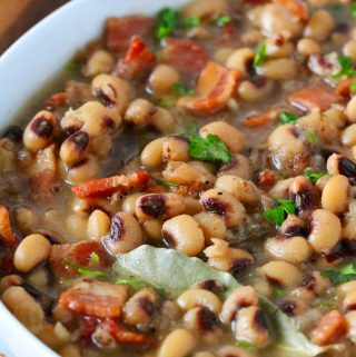 A close up shot of purple hull peas in a white bowl. Bacon and parsley are garnished across the top.