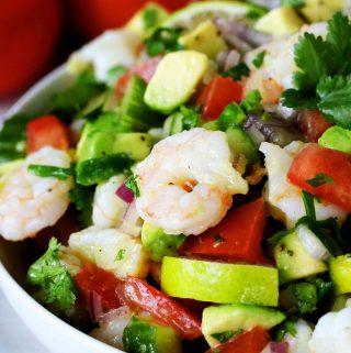 A close up shot of shrimp salad in a white bowl with tomato, avocado, lime, and cilantro.