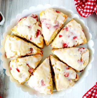 An overhead shot of 8 strawberry scones with glaze in a circular pattern on a cake stand.