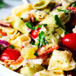 A close up shot of tortellini pasta salad in a bowl garnished with pepperoni.