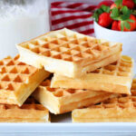 A square image of a stack of waffles on a platter with waffle mix and strawberries behind it.