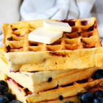 A stack of Blueberry waffles on a plate with blueberries surrounding it and butter on top.