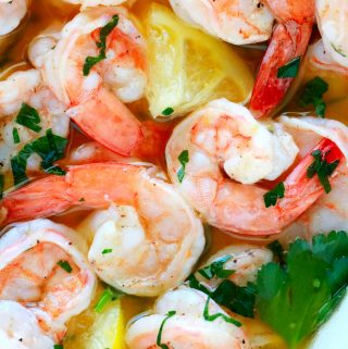 An overhead shot of garlic butter shrimp with parsley sprinkles and lemon wedges.
