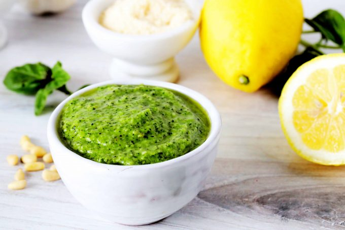 A bowl of creamy pesto with parmesan, lemon, basil, and pine nuts in the background.