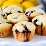 A cake stand with lemon blueberry muffins on top of it and lemons in the background.