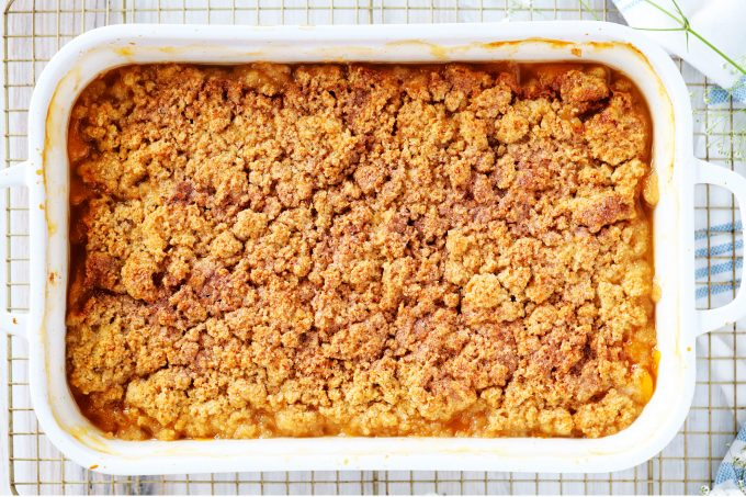 An overhead shot of old fashioned peach cobbler in a casserole dish.