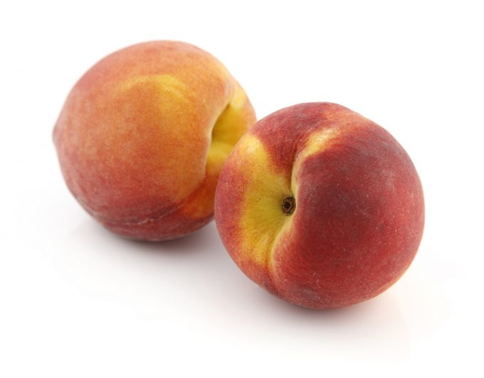 Two peaches on a white background.