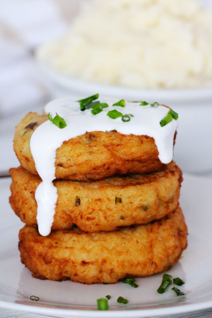 Potato Patties topped with sour cream with a bowl of mashed potatoes in the background.