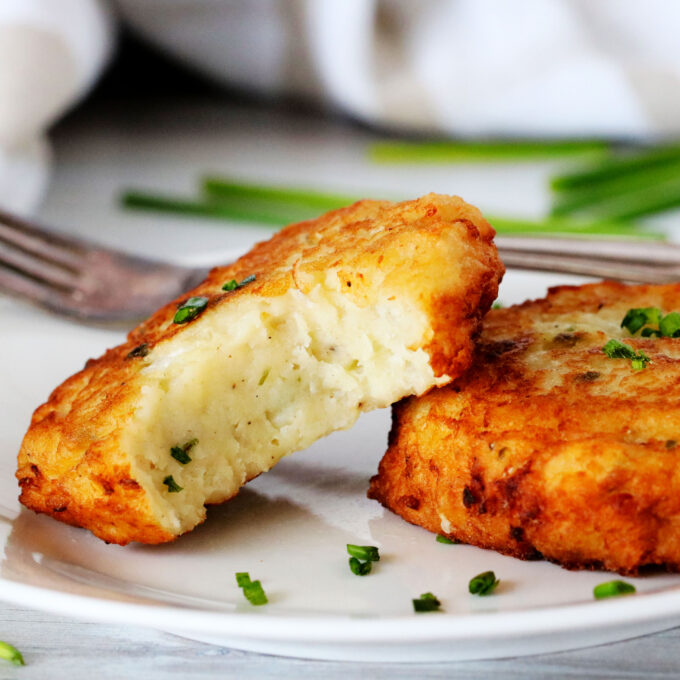 Two potato patties on a plate with chives scattered around them.