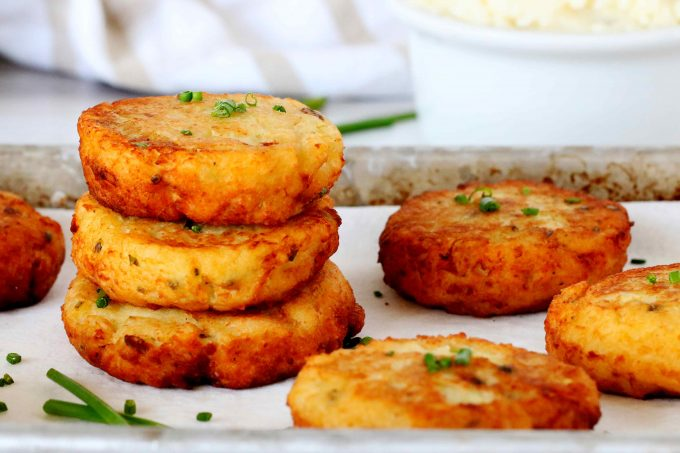 A stack of potato cakes on a paper towel lined sheet pan.