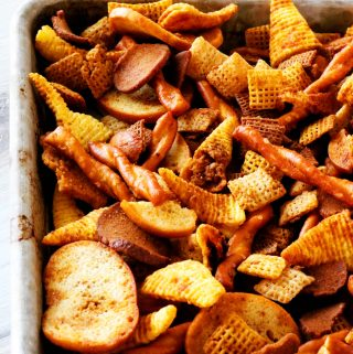 Different types of Chex cereal, pretzels, bagel chips, bugels, and rye chips on a sheet pan.