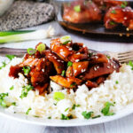 Baked Teriyaki Chicken over white rice on a plate with a casserole dish in the background.