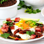 Huevos Motulenos on a white plate with refried beans in the background.
