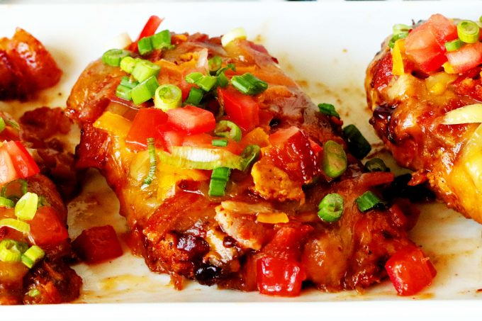 A platter of Monterey Chicken breasts topped with tomatoes and green onions.