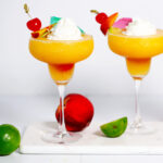 Two peach daiquiris in margarita glasses topped with fruited skewer, whipped cream, and a cocktail umbrella. They are on a white marble tray with peaches and limes around them.