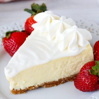 Sour cream cheesecake with strawberries next it on a white plate. There's a checkered towel and a baby's breath flowers in the background.