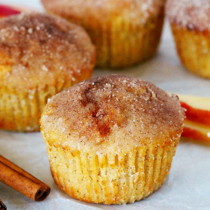 Apple cinnamon muffins with a cinnamon stick beside it and sliced apples in the background.