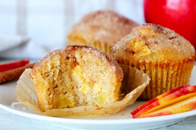 Apple Cinnamon Muffin with a bite taken out of it on a white plate.