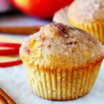 An apple cinnamon muffin with a cinnamon stick beside it and sliced apples in the background.