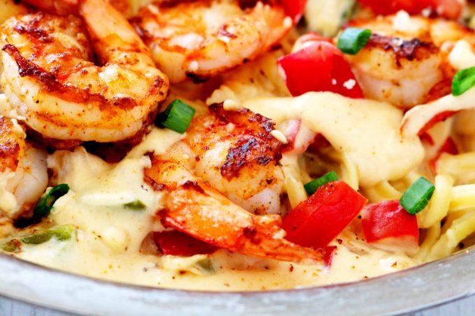 A close up shot of blackened shrimp in a pan with Cajun Alfredo sauce.