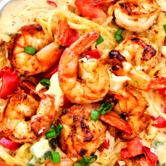 An overhead shot of Cajun Shrimp Pasta in a pan garnished with sliced green onions and diced tomatoes.