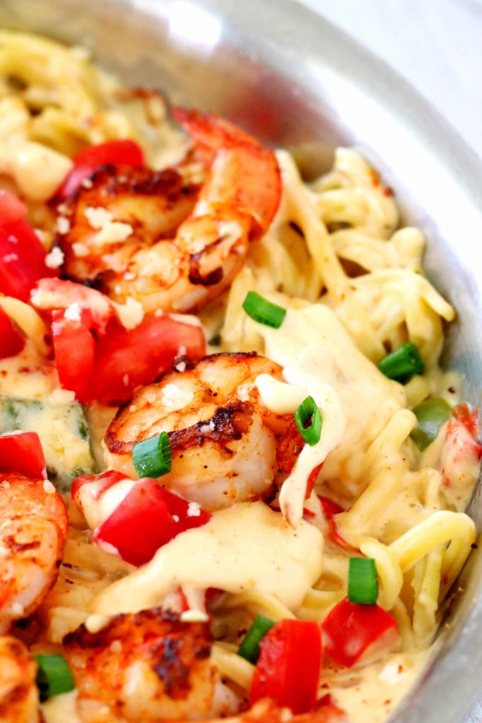 A close up shot of blackened shrimp with Fettuccini in a pan with Cajun Alfredo sauce.