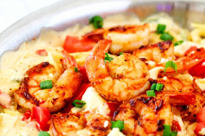 CA close up shot of Cajun Shrimp Pasta in a pan garnished with sliced green onions and diced tomatoes.
