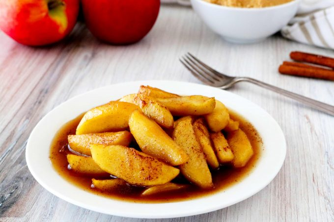 Fried apples on a white plate with a fork behind it.