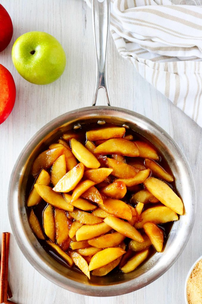 An overhead shot of a pan full of fried apples with apples and a striped dish towel off to the side.