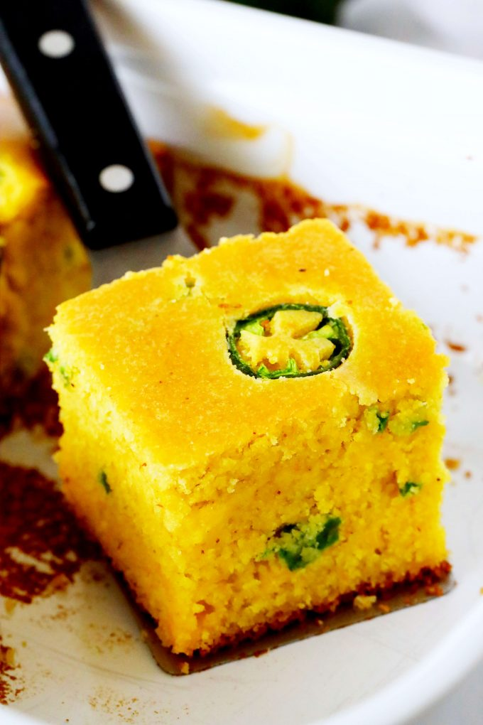 A slice of jalapeno cornbread on a spatula in a casserole dish.