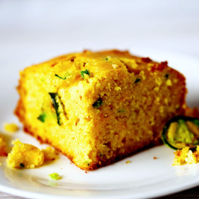A corner slice of jalapeno cornbread on a white plate.
